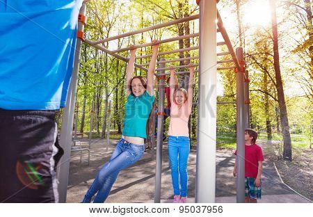 Hanging teens on horizontal bar at sports ground