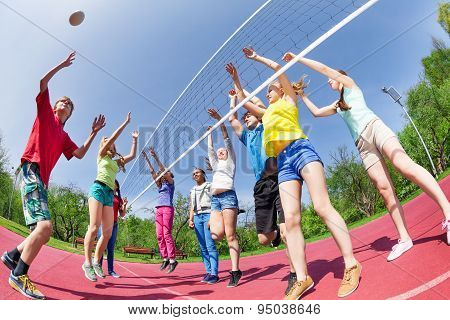 Fisheye view of teens playing volleyball on ground