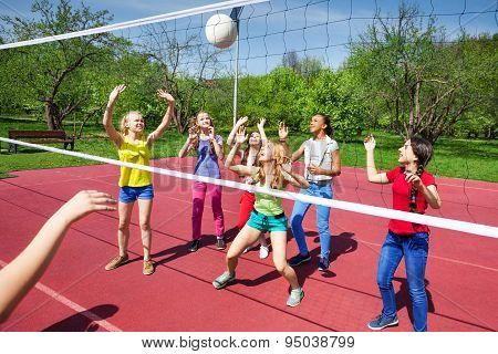 Volleyball net view on girls trying to catch ball