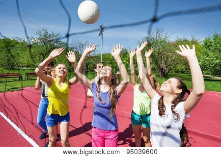 Teenagers are playing volleyball together near net