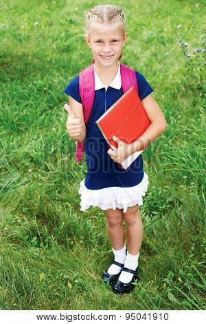 The Girl Has A Schoolbag And Books. Girl Shows Gesture Ok.