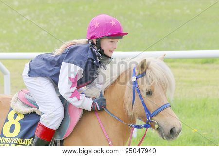 Young Smiling Girl Sitting On A Pony