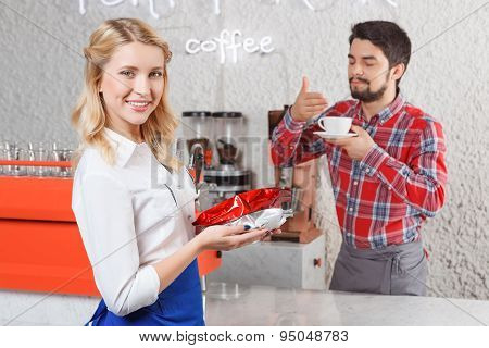 Female barista on background of satisfied customer