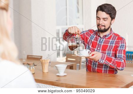Man pouring some espresso in cafe