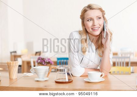 Pretty young waitress talking per mobile phone