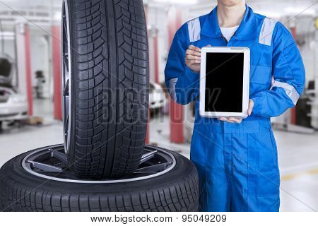 Mechanic Holds Tablet Near Tires
