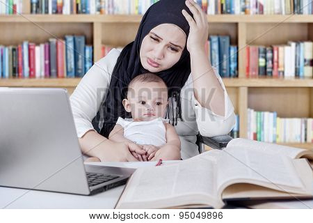 Stressful Mother Working In Library With Baby