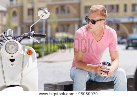 Handsome man sitting with coffee near his scooter