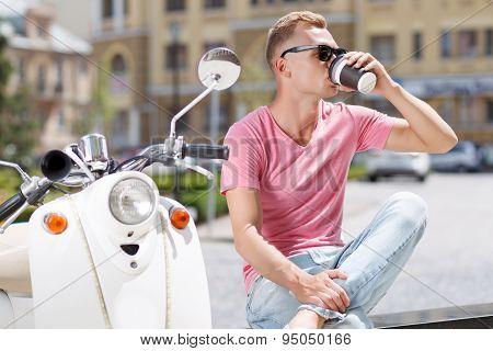 Handsome man drinking coffee in park