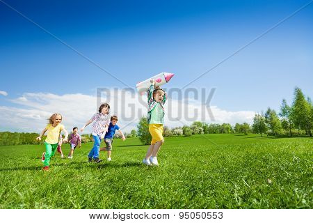 Children run after boy holding rocket carton toy