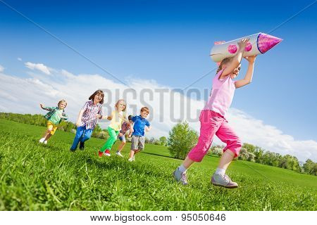 Small girl holding rocket carton toy and kids run