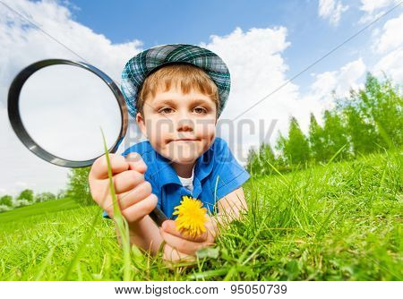 Small boy with hat holds magnifier laying on grass