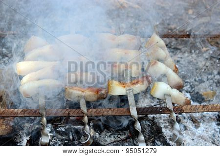 fried pieces of lard cooking on the fire