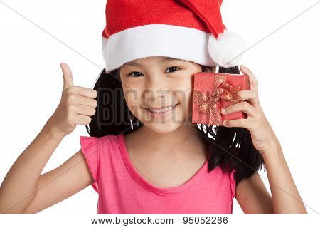 Happy Little Asian Girl Show Thumbs Up With Santa Hat And Gift Box