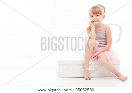 Pretty little girl sitting on case