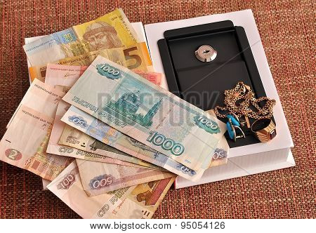 Ruble, Hryvnia, Jewelry And Mini-safe On A Homogeneous Background