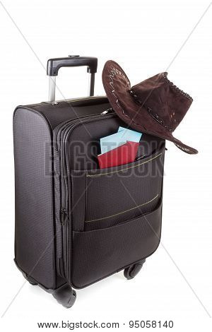 Suitcase with hat on it isolated against a white background. Travel concept