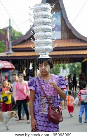 Mon girl carries pots on her head