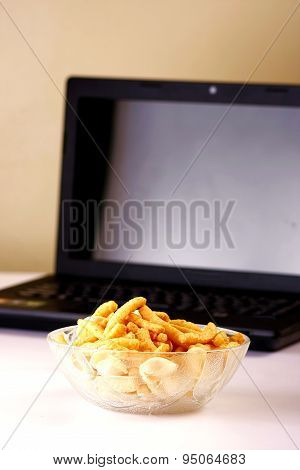 Bowl of chips or junk food and a laptop computer in the background