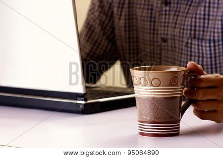 Coffee mug held by a man working on a laptop computer in the background
