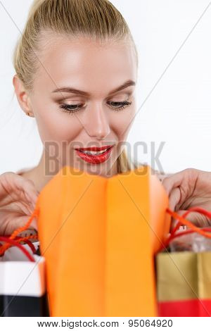 Blond Woman Inspecting Content Of Colored Paper Bags