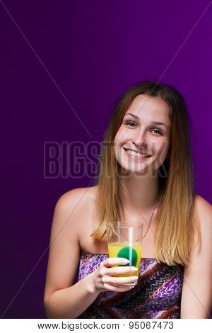 girl drinking a cocktail against violet background
