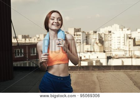 smiling lady with towel around neck after workout