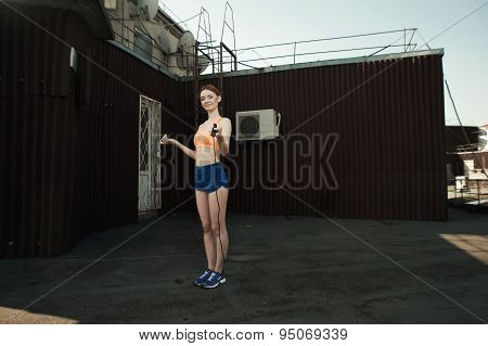 exhausted sexy lady with skipping rope on roof