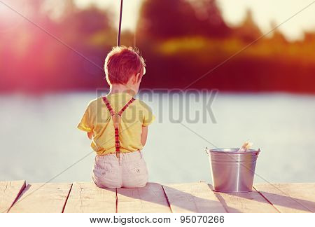Cute Little Boy Fishing On Pond At Sunset