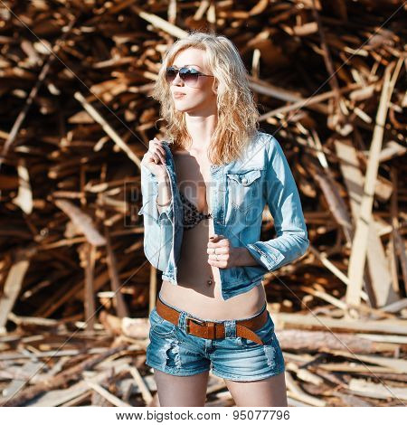 Beautiful Woman In Denim Jeans Shorts And Jacket. Standing On The Background The Sawmill