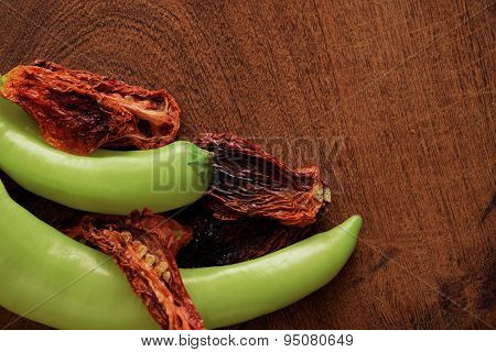 Sun Dried Tomatoes And Green Peppers On A Cutting Board