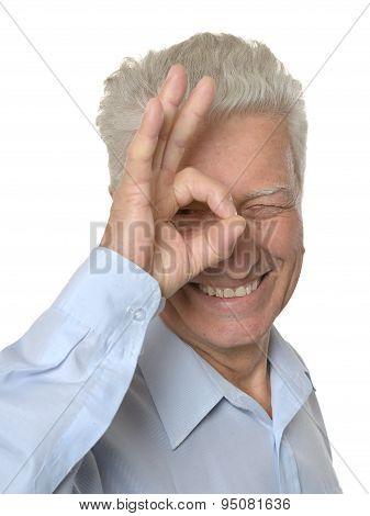 Happy senior man showing ok