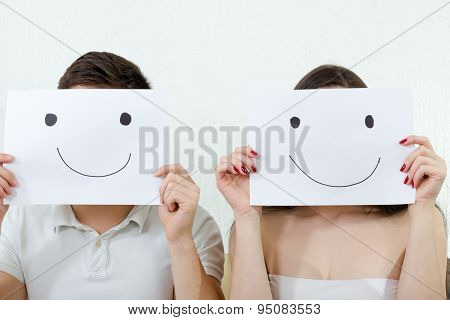 Happy Couple Holding Smileys Over Their Faces