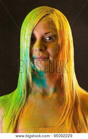 portrait of attractive woman with green and yellow colors Holi
