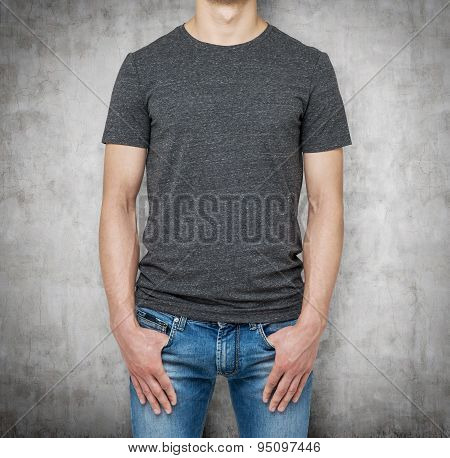 Close-up Of A Man In A Blank Grey T-shirt. Hands In The Denims Pockets. Concrete Background.