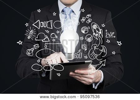 Businessman Is Looking For New Business Ideas In Tablet. Flying Business Icons And A Light Bulb As A