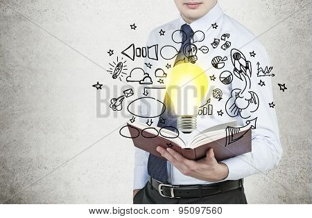 Young Businessman Is Holding A Book With Flying Around Business Icons And A Light Bulb As A Concept