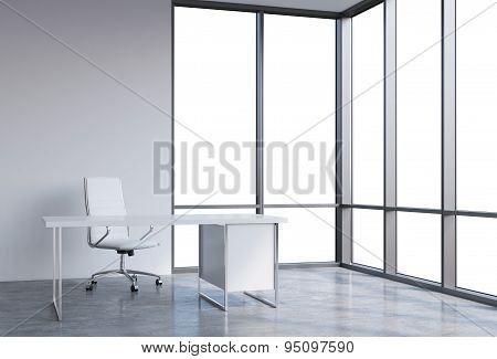 A Workplace In A Modern Corner Panoramic Office, Copy Space On Windows. A White Leather Chair And A