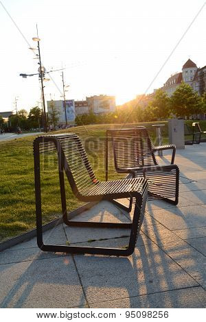 Iron Chairs At Main Railway Station Building At Sunset.