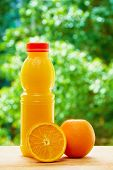 foto of orange  - Vertical photo of bottle of orange juice and the orange and the half of orange on the wooden table on the green blurred background - JPG