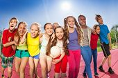 picture of volleyball  - Happy friends standing on the volleyball game court holding ball during summer sunny day - JPG