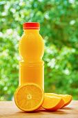 stock photo of orange  - Bottle with orange juice and the half of orange and the two orange lobules on the wooden table on the green blurred background - JPG