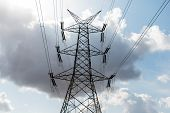 stock photo of power transmission lines  - High voltage transmission line tower against a cloudy sky - JPG