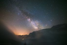 stock photo of italian alps  - The Milky Way and the starry sky captured at high altitude on the Italian French Alps with glowing valley below - JPG