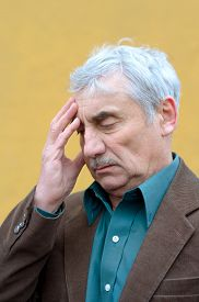stock photo of frown  - Stressed caucasian senior man with headache put his hand on his forehead frowning looking down - JPG