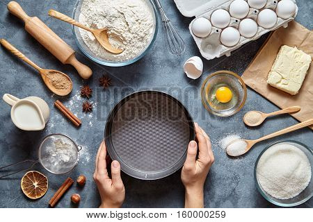 The process of making pie dough by hand. Baking cake in kitchen - dough recipe ingredients eggs, flour, milk, butter, sugar on table. Top view. Flat lay.