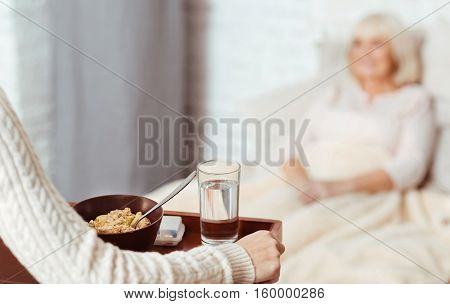 Its time to eat. Selective focus of tray with breakfast in hands of pleasant woman holding it and going to elderly woman