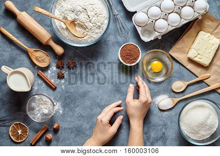 The woman's hand ready to knead the preparing ginger cake. Work with the dough. The kitchen table raw ingredients with eggshell, rolling and baking pin.