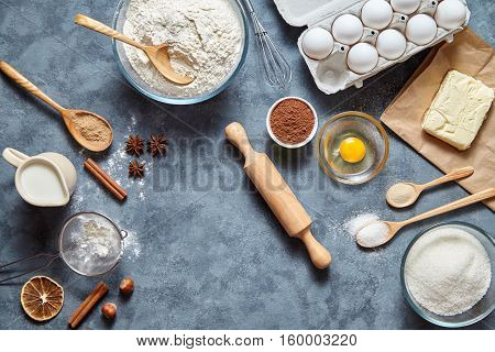 The process Baking cake in kitchen - dough recipe ingredients eggs, flour, milk, butter, sugar on table from above. Bake sweet cake dessert concept. Top view.