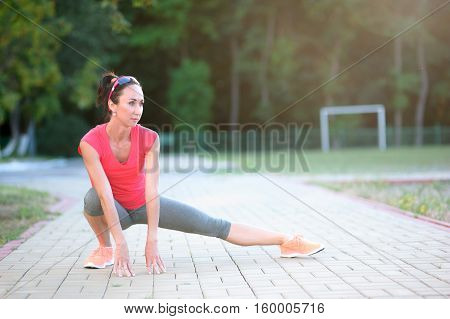 beautiful athletic female in sport bra stretching outdoors in sunny summer day adult fit woman with perfect body at physical exercises in the fresh air before running
